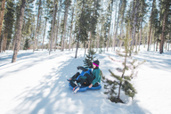 High angle view of mother and son sliding on snow covered field against trees - CAVF10512