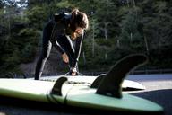 Woman wearing wetsuit preparing surfboard at beach - CAVF10539