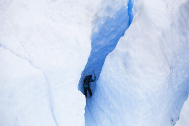 Low angle view of man climbing snow covered mountain - CAVF10575