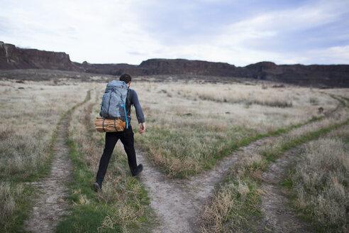 Rear view of hiker walking on field against sky - CAVF10578