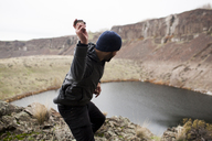 Side view of hiker throwing stone in lake while standing on cliff - CAVF10587