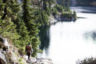 High angle view of hiker and dog standing on rocks by Snow Lake - CAVF10593