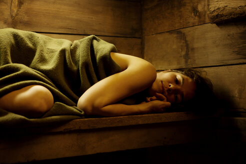 Woman wrapped in blanket relaxing in sauna - CAVF10600