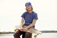 Portrait of man with longboard sitting on wooden post against clear sky - CAVF10651
