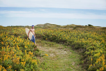 Man carrying surfboard while walking on field against sky - CAVF10657