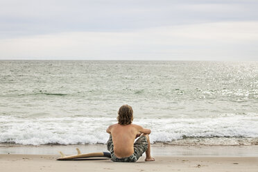 Rear view of man with surfboard sitting at shore - CAVF10666