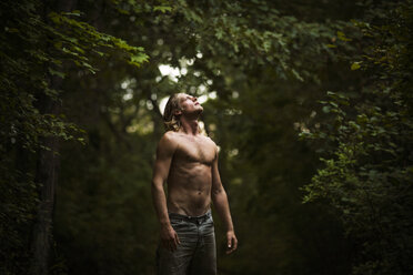 Shirtless man looking up while standing in forest - CAVF10672