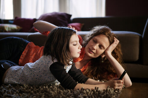 Mother and daughter lying on rug at home - CAVF10720