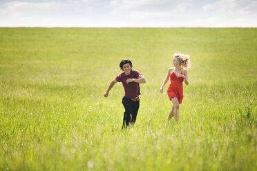 Couple running on grassy field - CAVF10741