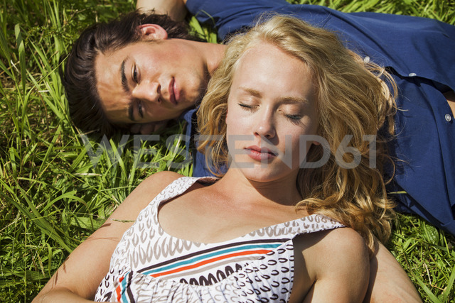 High angle view of couple relaxing on grassy filed - CAVF10747 - Cavan Images/Westend61