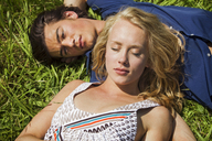 High angle view of couple relaxing on grassy filed - CAVF10747