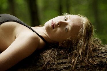 Portrait of sensual woman lying on tree trunk - CAVF10765