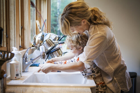 Mother assisting son in washing hands at kitchen sink - CAVF10852