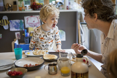 Father and son playing at dinning table in home - CAVF10873