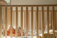 Portrait of cute boy lying in crib at home - CAVF10882