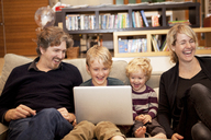 Siblings using laptop while sitting with parents on sofa at home - CAVF10933