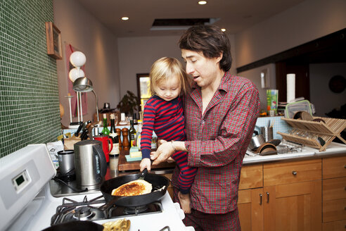 Father and son cooking pancake in kitchen at home - CAVF10939
