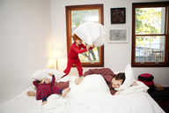 Family having pillow fight on bed at home - CAVF10948