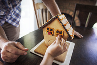 Cropped image of boy decorating gingerbread house at home - CAVF11059