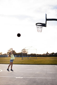 Girl throwing basketball to make a goal on court against sky - CAVF11074