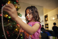 Girl decorating Christmas tree at home - CAVF11077
