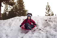 Boy screaming while tobogganing on sled at snowfield - CAVF11086
