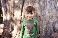 Portrait of cute boy standing against tree trunk - CAVF11101