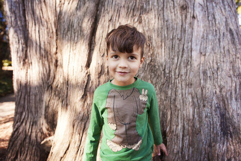 Portrait of cute boy standing against tree trunk - CAVF11101