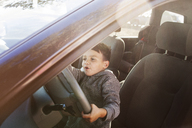 Boy pretending to drive while sitting in car - CAVF11146