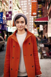 Portrait of woman standing on sidewalk in city - CAVF11167