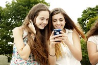 Female friends smiling while looking at mobile phone - CAVF11191