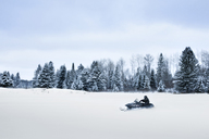 Man riding snowmobile on landscape against sky - CAVF11212