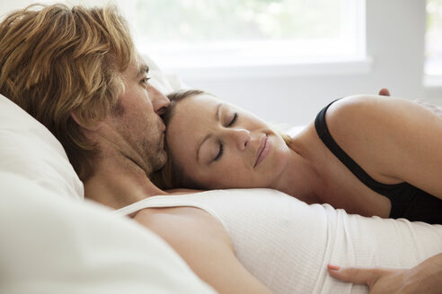 Boyfriend kissing girlfriend on forehead while lying on bed - CAVF11230