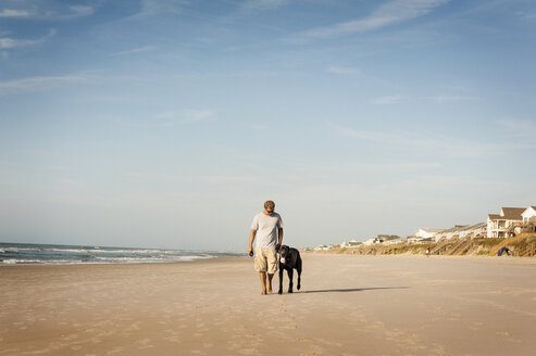 Man walking with dog on shore against sky - CAVF11251