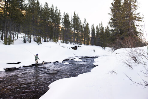 Man fly-fishing in river amidst snow covered land - CAVF11263