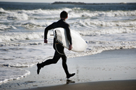 Rear view of surfer carrying surfboard while running on shore at beach - CAVF11269