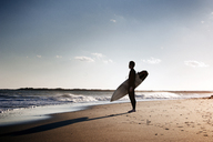 Side view of surfer carrying surfboard while standing on shore at beach - CAVF11275