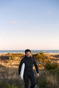 Surfer carrying surfboard while walking on grassy field against sky - CAVF11278