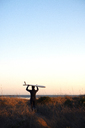 Rear view of surfer carrying surfboard on head against clear sky - CAVF11281