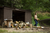 Lumberjack holding wood log by shed in forest - CAVF11335