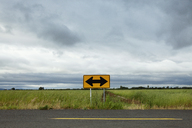 Arrow symbol on empty road by field against cloudy sky - CAVF11347