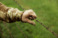 Cropped image of farmer holding barbed wire fence - CAVF11356