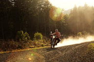 Man riding motorcycle on gravel road - CAVF11401