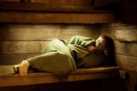 Man wrapped in blanket relaxing in sauna - CAVF11419