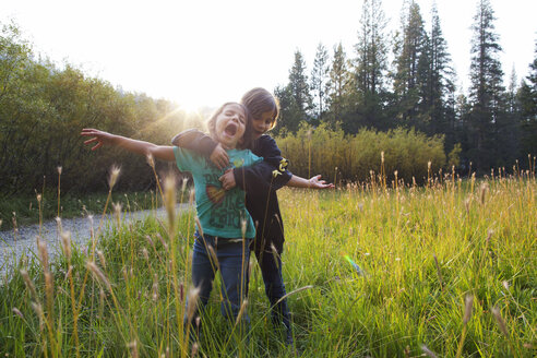 Girl embracing friend while standing on grass against sky - CAVF11656