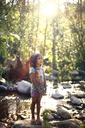 Girl looking up while standing by river at forest - CAVF11722