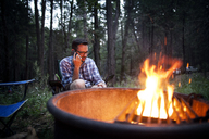 Man using mobile phone while sitting by bonfire in forest - CAVF11785
