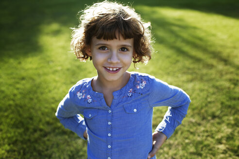 Portrait of girl standing with hands on hip at park - CAVF11800
