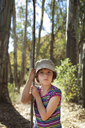 Portrait of girl holding stick while standing in forest - CAVF11827