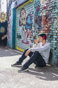 Young man with headphones sitting in front of graffiti wall using cell phone - AFVF00311